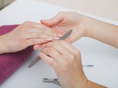 Woman hands in a nail salon receiving a manicure procedure. SPA manicure. 写真素材 - 129786320