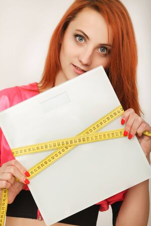 Diet. woman holding weight scale and measuring