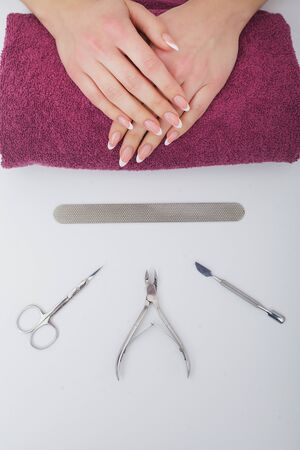 Woman Hand Care. Closeup Of Beautiful Female Hands Having Spa Manicure At Beauty Salon. Beautician Filing Clients Healthy Natural Nails With Nail File. Nail Treatment. High Resolution 写真素材