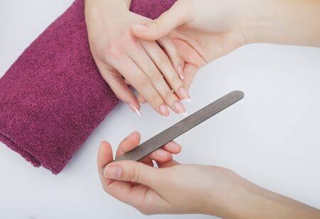 Woman hands in a nail salon receiving a manicure procedure. SPA manicure. 写真素材 - 129838422