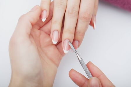 Woman hands in a nail salon receiving a manicure procedure. SPA manicure. 写真素材 - 129838275