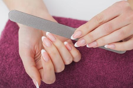 Woman Hand Care. Closeup Of Beautiful Female Hands Having Spa Manicure At Beauty Salon. Beautician Filing Clients Healthy Natural Nails With Nail File. Nail Treatment. High Resolution 写真素材 - 129838280