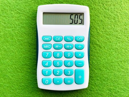 Top view of a calculator on green background