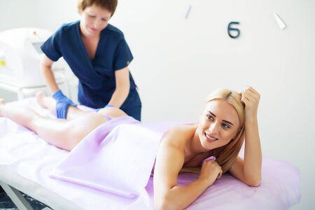 Protección de la piel. La mujer está en proceso de lipomasaje en la clínica.