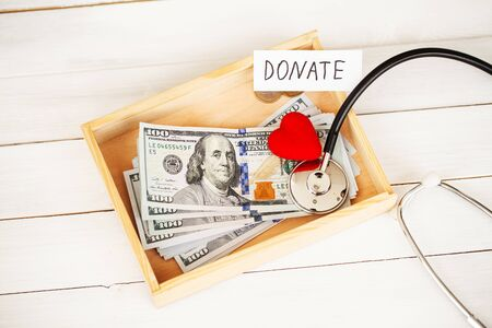 Donate conception. Box with money on white wood background Stock Photo