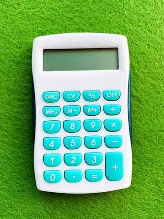 Top view of a calculator on green background.