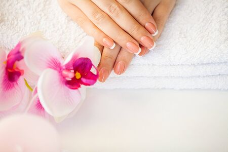 Beautiful womans nails with french manicure, in beauty studio