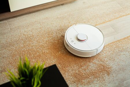 Smart home. Robot vacuum cleaner performs automatic cleaning of the apartment at a certain time Фото со стока