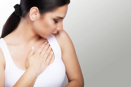 Pain. Close-up of a young woman feels severe chest pain. Close-up of a womans body with a hand on her chest. The girl suffers from a painful feeling that has a health problem. Stock fotó
