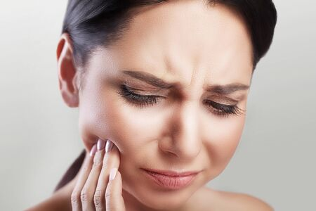 Toothache in a young beautiful woman. Caries. A woman holds her hand in the teeth area. A painful sensation. The concept of health. On a gray background.