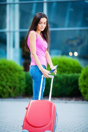 Vacation. Smiling female passenger proceeding to exit gate pulling suitcase through airport concourse