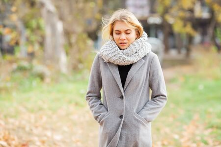 Cold and flu. Young woman in a gray coat walking in the autumn park and warms frozen hand