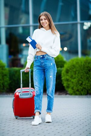 Pretty business woman with red suitcase near airport flies on vacation on sea