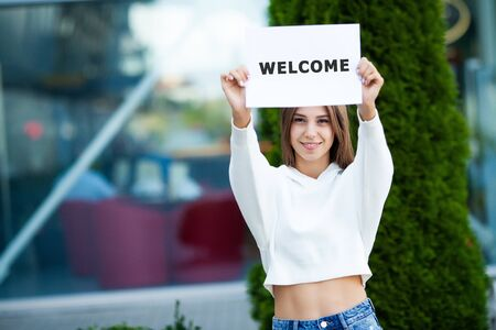 Businesswoman with long Hair Holding a sign Board with a Welcome has Airport Background Stok Fotoğraf