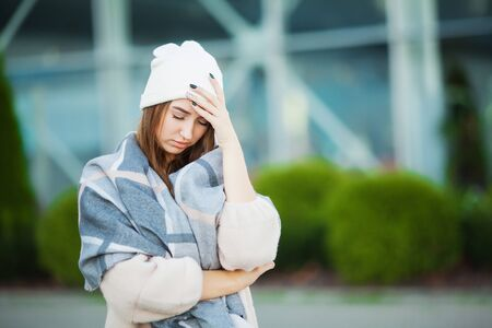 Cold and flu. Woman with flu outdoors dressed in cap