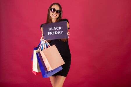 Black Friday. Woman with the inscription Black Friday and gift bags on a red background