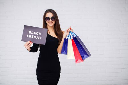 Black Friday. Woman with the inscription Black Friday and gift bags on a white background