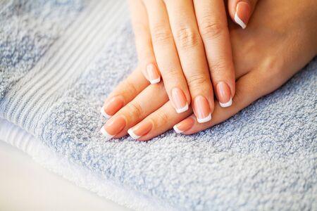 손톱 관리. 뷰티 스튜디오에서 프랑스 매니큐어로 아름다운 여성의 손톱 스톡 콘텐츠
