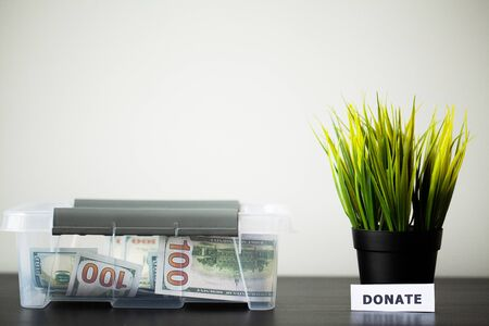 Donate box with dollars on wood desk Banque d'images - 131915156