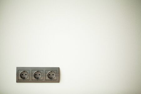 Closeup view of a group of gray european electrical outlets located on a gray wall