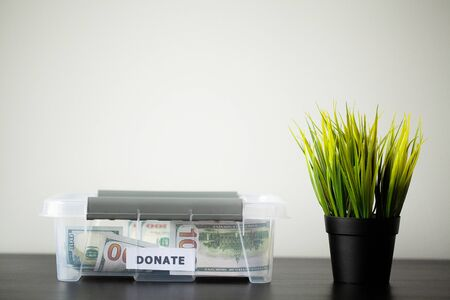 Donate box with dollars on wood desk Banque d'images - 131915254