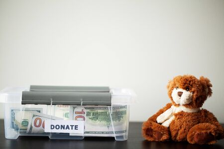 Donate box with dollars on wood desk Banque d'images - 131915260