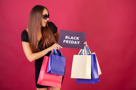 Black Friday. Woman with the inscription Black Friday and gift bags on a red background.