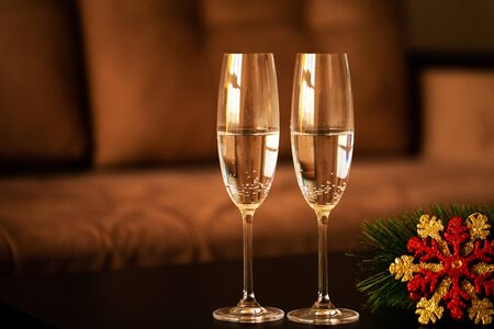 Glasses filled with champagne on Christmas background