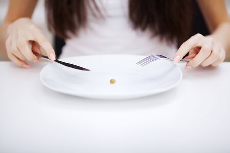 Eating disorder. Girl is holding a plate and trying to put a pea on the fork Reklamní fotografie