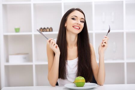 Diet concept, green apple on a white plate, fork, knife, weight loss, healthy diet, yellow measuring tape, weight loss