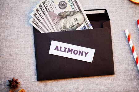 Alimony in a black envelope on a Christmas background