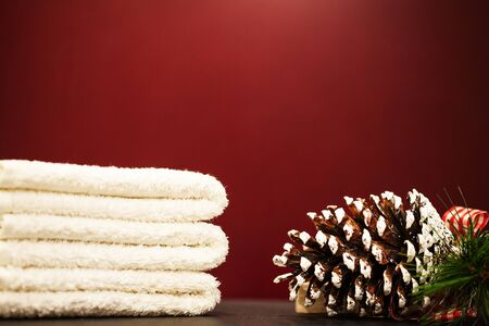 Christmas decoration and spa towels on red background