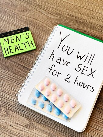 Pills for men's sexual health and notepad with text.