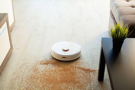 Smart House. Vacuum cleaner robot runs on wood floor in a living room