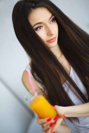 Cheerful woman drinking an orange juice sitting on her bed at home Banque d'images - 137185726