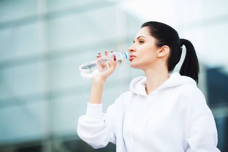 Sport outdoor. Woman Drinking Water After Running Stockfoto