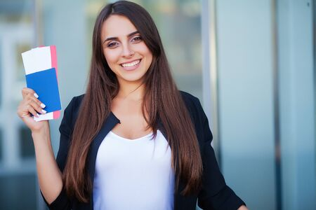 Woman holding two air ticket in abroad passport near airport Reklamní fotografie