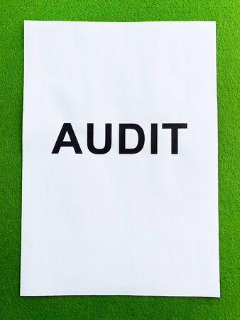 Document with title audit on green background, top view