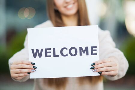 Women business with the poster with welcome message. Stok Fotoğraf
