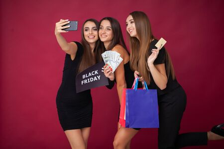 Three women holding discount blank on red background in black friday holiday