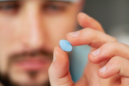 Close up of male doctor holding pill for men health Stock Photo
