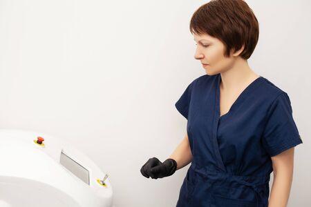 Cosmetologist doctor prepares to laser epilate client in beauty studio. Standard-Bild