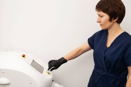 Cosmetologist doctor prepares to laser epilate client in beauty studio