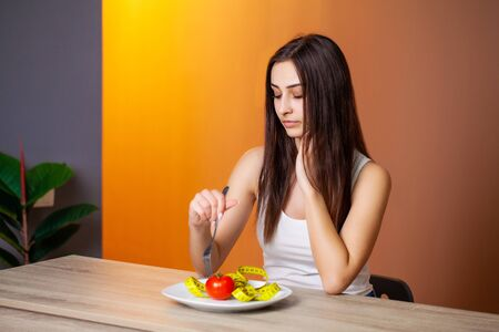 Portrait of young beautiful woman with tomato and measuring tape on plate