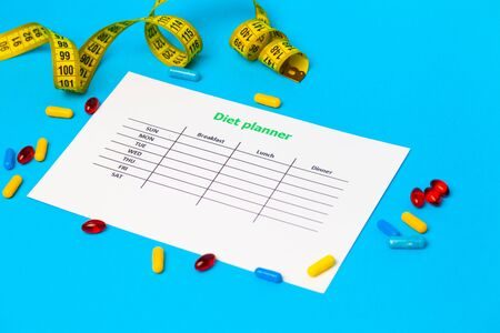 Diet plan and weight loss pills on the blue background