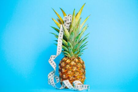 Ripe pineapple with measuring tape on a blue background.