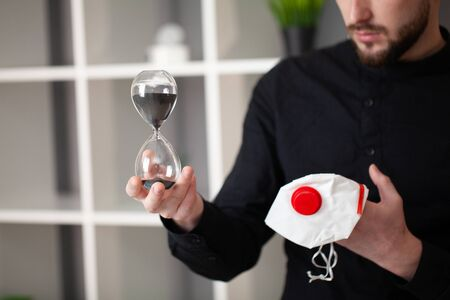 Man holds a mask and an hourglass that indicates that time is burning