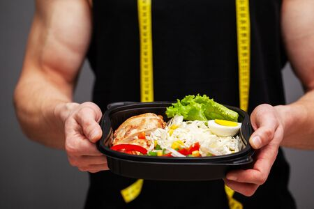 Closeup of a man holding a box full of protein rich foods for sports nutrition Banque d'images