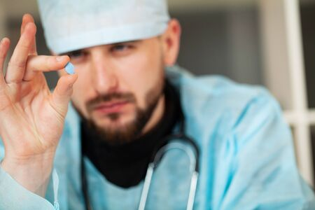 Doctor holds a pill for mens health Stock Photo