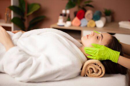 Pretty woman receiving facial massage in spa salon.